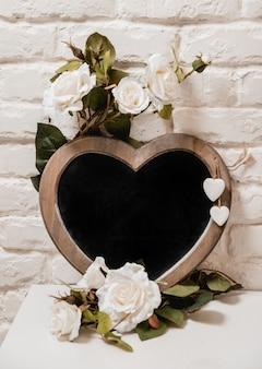 El marco como un corazón con flores en la pared.