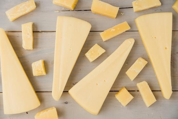 Marco completo de queso triangular y cubo en escritorio de madera