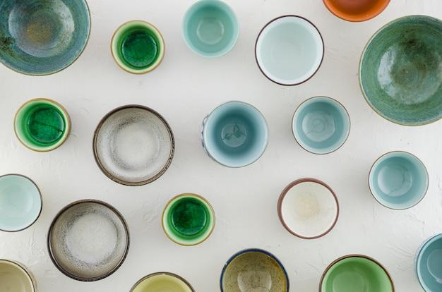 Marco completo de tazones de cerámica y vidrio y tazas de té sobre fondo blanco