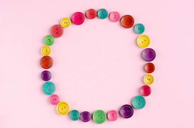 Marco de composición de botones de costura color sobre fondo rosa.