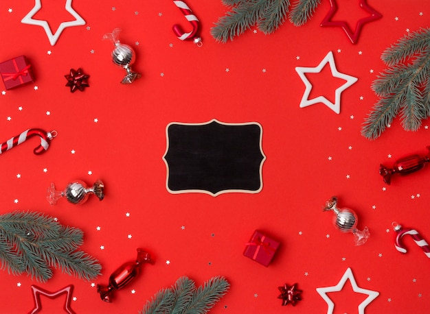 Marco de composición navideña hecha de ramas de abeto, arcos, regalos, bastones de caramelo y adornos de estrellas en mesa roja