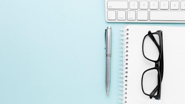 Marco de concepto de escritorio con gafas y bolígrafo