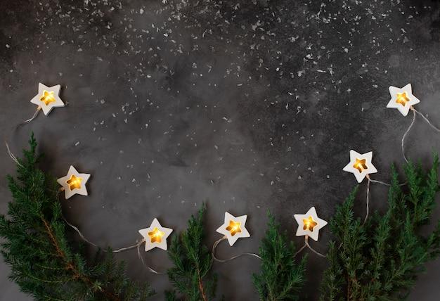 Marco de concepto de navidad o año nuevo con decoraciones de vacaciones de invierno. fondo oscuro con una guirnalda ardiente. copia espacio