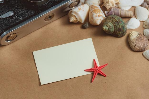 Marco de conchas y cámara fotográfica sobre fondo claro con tarjeta en blanco