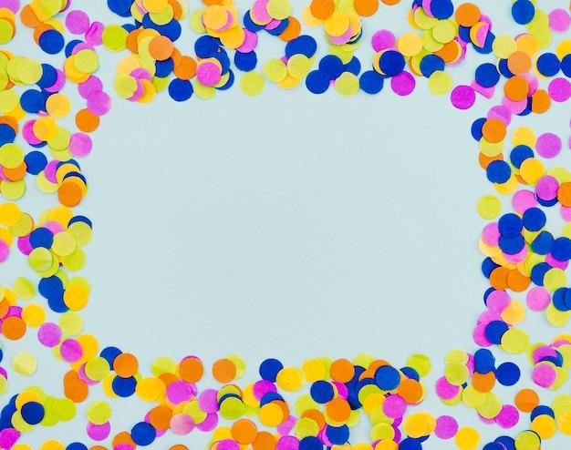 Marco de confeti de colores sobre fondo azul
