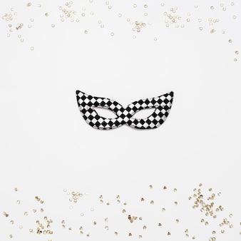 Marco de confeti dorado y máscara de carnaval