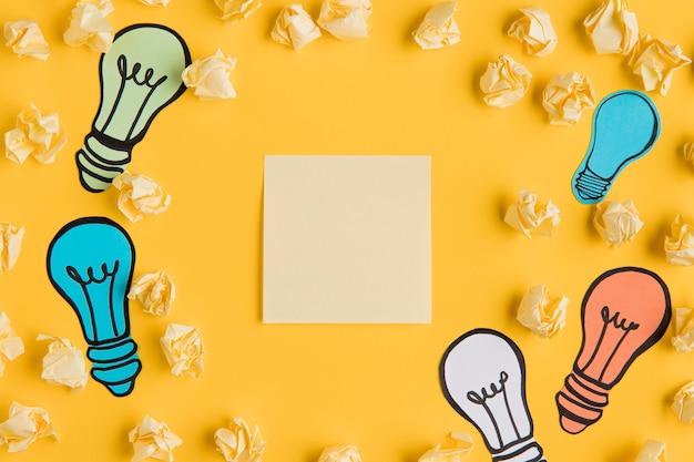 Marco con conjunto de bombilla ligh y hoja de papel en blanco