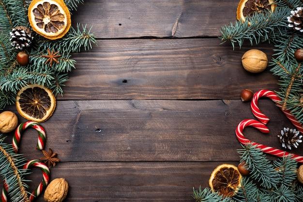 Marco de conos de árbol de navidad naranjas caramelo nueces de caña sobre fondo de madera oscura. copia espacio endecha plana.