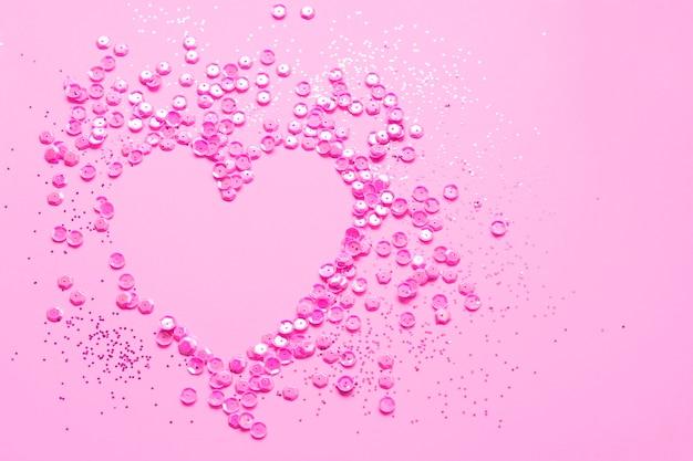 Marco de corazón hecho de lentejuelas rosas y purpurina sobre un fondo rosa