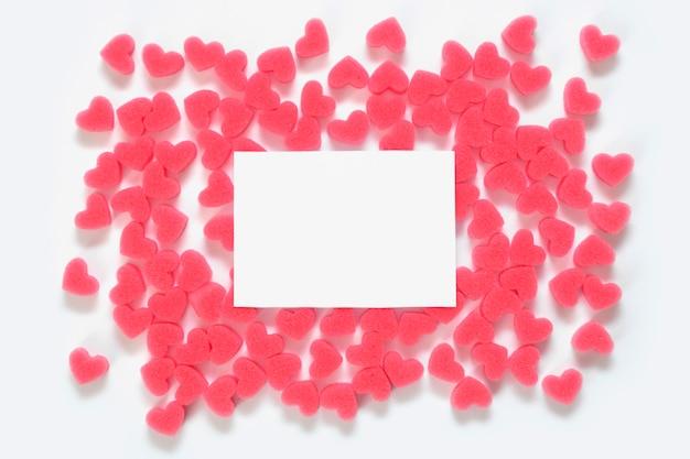 Marco de corazones de color rosa suave en una pared blanca con espacio de copia.