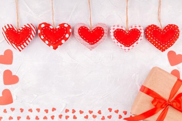 Marco de corazones de confeti y textiles hechos a mano y caja de regalo con lazo de cinta roja