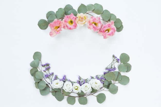 Marco de corona de flores hecho de diferentes flores y hojas, fondo plano, vista superior