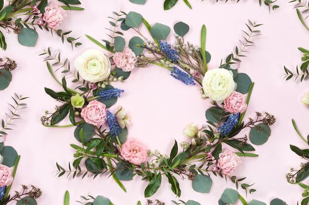 Marco de corona de flores con ramas frescas de rosas en forma de pión y hojas de eucalipto aisladas sobre fondo blanco, plano y vista superior