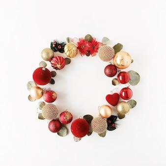 Marco de corona de navidad hecho de bolas de navidad de colores brillantes sobre fondo blanco.