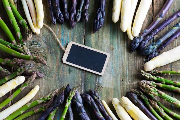 Marco creativo de espárragos orgánicos naturales recién escogidos y pizarra para mensaje sobre un fondo de madera.