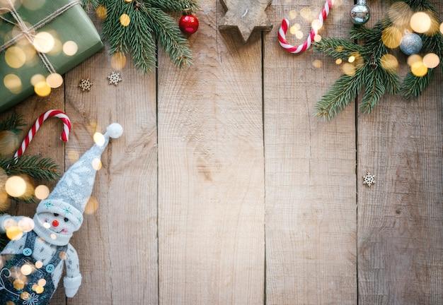 Marco creativo navideño con decoración de invierno de muñeco de nieve, cajas de regalo, bastones de caramelo y ramas de pino con espacio de copia