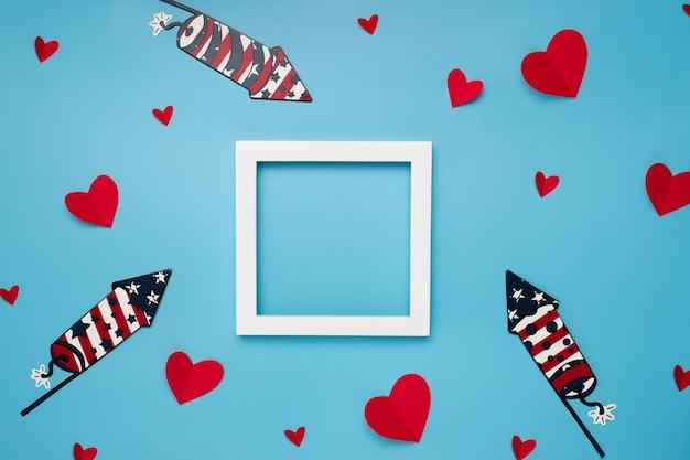 Marco cuadrado blanco sobre fondo azul con corazones de papel y fuegos artificiales para el día de la independencia