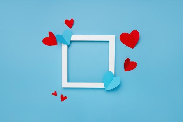 Marco cuadrado blanco sobre fondo azul con corazones de papel