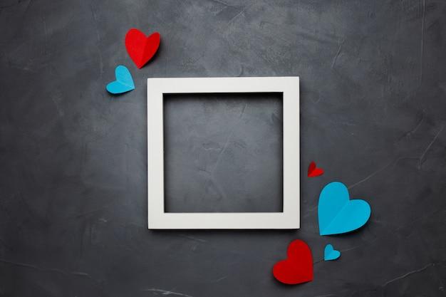 Marco cuadrado blanco vacío con corazones sobre fondo gris texturizado con copyspace