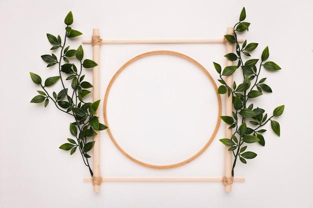 Marco cuadrado y círculo de madera decorado con hojas verdes sobre fondo blanco.