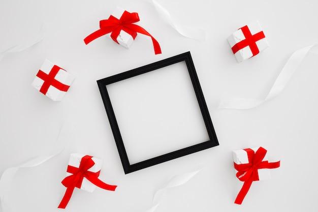 Marco cuadrado negro con dos corbata roja y regalos de navidad sobre fondo blanco.