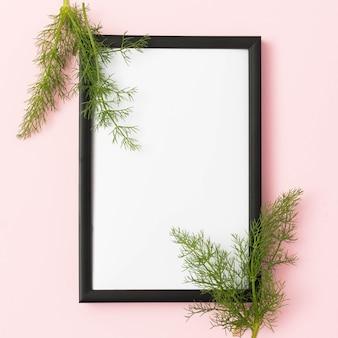 Marco de cuadro vacío con hojas de hinojo sobre fondo rosa