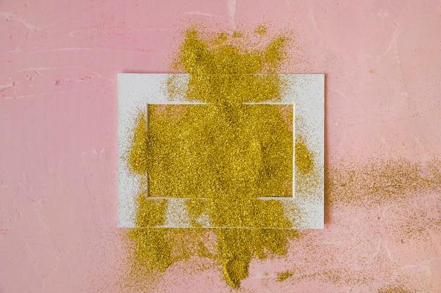 Marco cubierto con lentejuelas amarillas en mesa rosa.