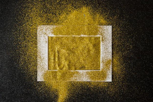 Marco cubierto con lentejuelas amarillas en mesa.