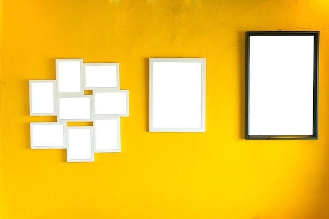 Marco de fotos en blanco en la pared amarilla de la vendimia.