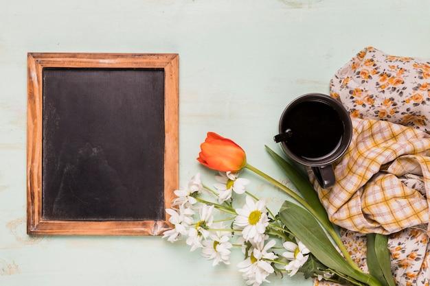 Marco decorado de pizarra con flores y taza.