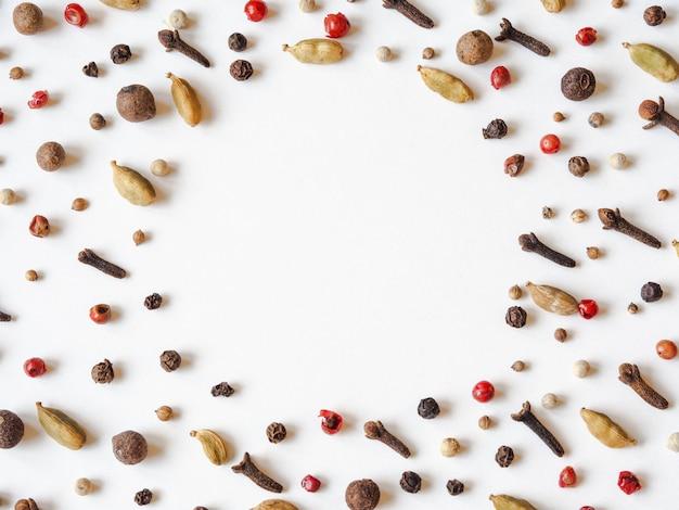 Marco decorativo creativo de la composición de alimentos de diversas especias en el fondo blanco.