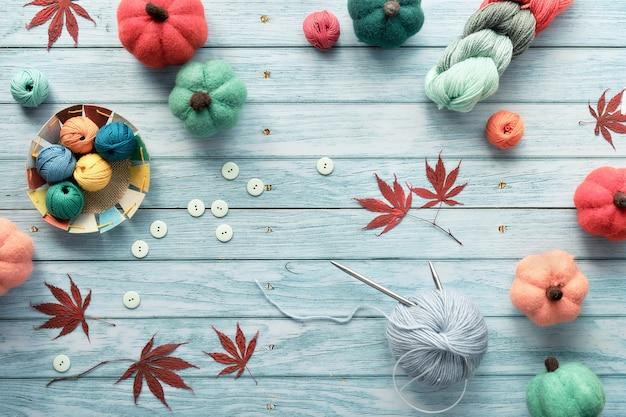Marco decorativo de manojos de lana, ovillos de lana, calabazas de fieltro decorativo, hojas de otoño de arce rojo.