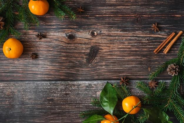 Marco decorativo de navidad de mandarinas, ramas de abeto, piñas, canela, anís estrellado. fondo de invierno con espacio de copia