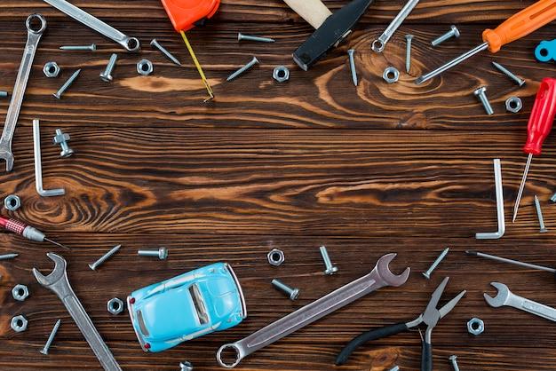 Marco de diferentes herramientas y coche de juguete.