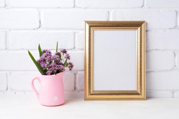Marco dorado con flores de color púrpura en jarra rústica rosa