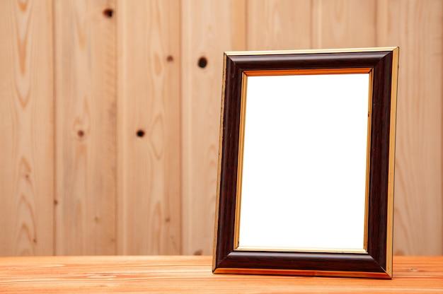 Marco dorado con inserto de madera para fotos y pinturas sobre un fondo de madera