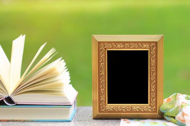 Marco dorado con libros en mesa de madera.