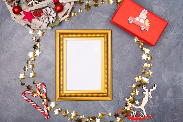 Marco dorado con papel en blanco rodeado de elementos navideños