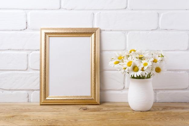 Marco dorado con ramo de manzanilla en florero rústico