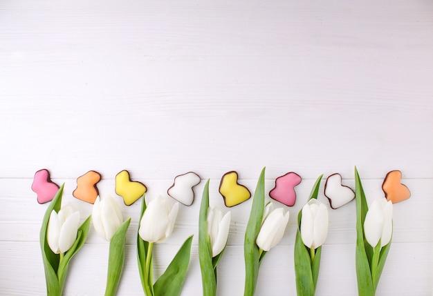 Marco de dulces para celebrar la pascua. conejito colorido chocolate y tulipanes blancos.