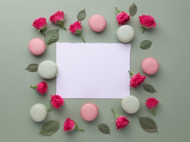 Marco encantador romántico de macarons y rosas sobre fondo verde. endecha plana. vista superior