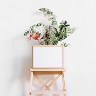 Marco enfrente de plantas en taburete