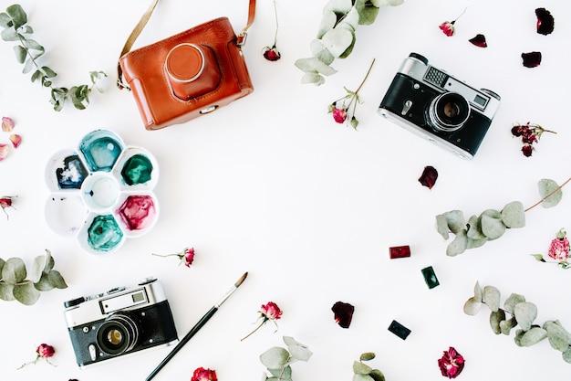 Marco del espacio de trabajo del artista con cámara de fotos retro vintage y arreglo de acuarela, rosas rojas y eucalipto