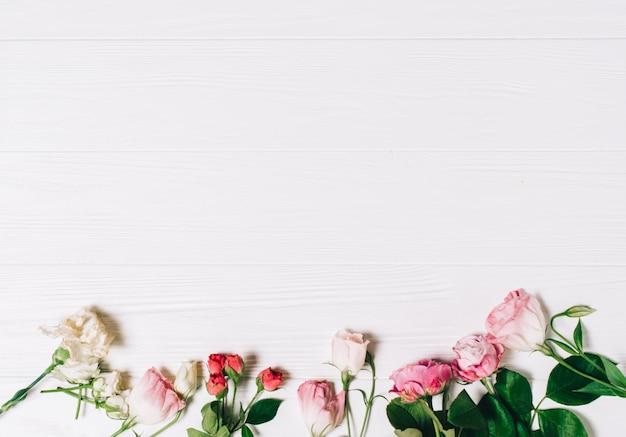 Marco femenino del espacio de trabajo del escritorio con las rosas y los pétalos rosados en fondo de madera blanco. piso plano, vista superior. flor de fondo. día de la mujer, día de la madre.