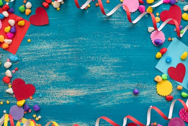 Marco festivo del fondo con la decoración de los corazones del caramelo del confeti de las flámulas.