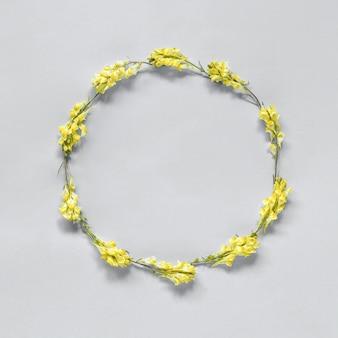 Marco floral corona redonda de flores amarillas sobre gris