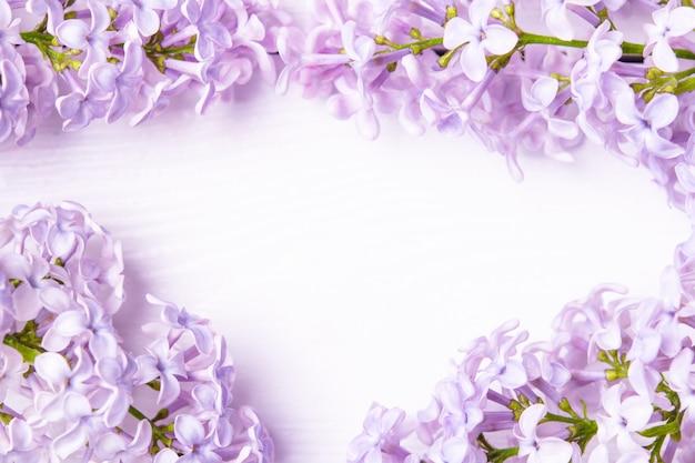 El marco floral hecho de las flores de la lila de la primavera se cierra para arriba. flores de primavera