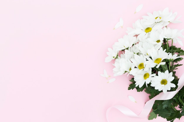Marco floral plano laico con fondo rosa