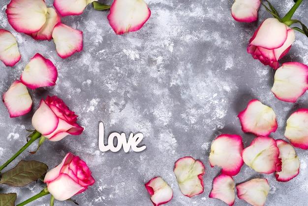 Marco floral: ramo de rosas blancas rosadas y cajas de regalo en el fondo de piedra