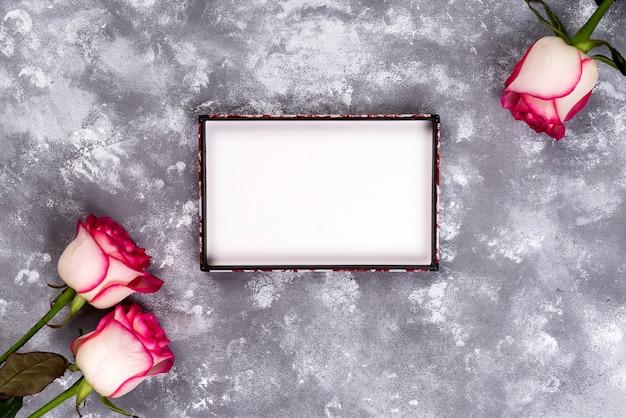 Marco floral: ramo de rosas blancas rosadas en el fondo de piedra con el espacio de la copia para el texto.